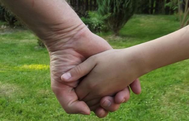 W ojcowskiej dłoni dziecięca dłoń czuje się bezpieczna