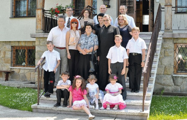 Ks. Zbigniew Kras na schodach lipnickiej plebanii w otoczeniu parafian