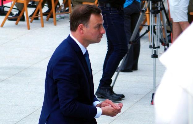 Prezydent Andrzej Duda niesie konsekrowaną Hostię na ołtarz