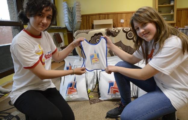 Wolontariusze trzymający śliniaczek dla najmlodszego uczestnika ŚDM