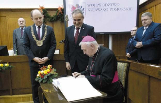 Bp Andrzej Suski dokonuje wpisu do księgi pamiątkowej