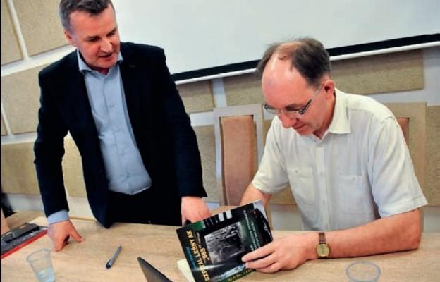 Janusz Skowroński podpisuje książkę wójtowi gminy Biłgoraj Wiesławowi Różyńskiemu