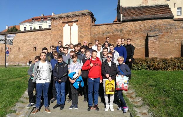 Na tle średniowiecznych murów obronnych miasta Torunia z proboszczem katedry ks. prał. Markiem Rumińskim