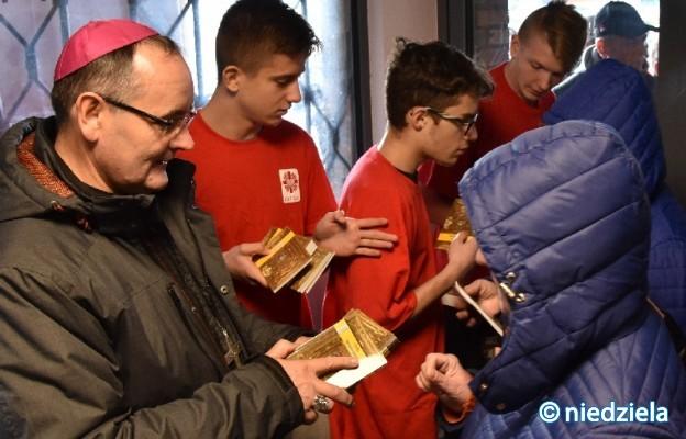 Bp Andrzej Przybylski i iwolontariusze Caritas rozdają podczas pielgrzymki osób bezdomnych egzemplarze Ewangelii, prezent od