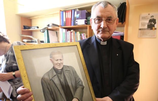 Ks. Andrzej Dziełak, postulator  z portretem sługi Bożego ks. Aleksandra Zienkiewicza