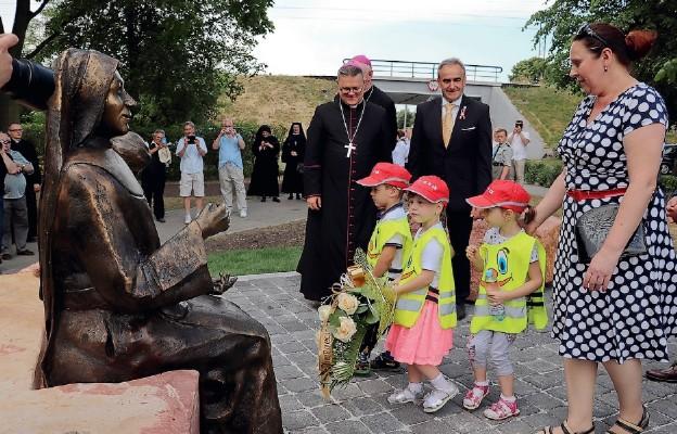 """Dzieci z Niepublicznego Przedszkola """"Aniołkowo"""" składają kwiaty przy pomniku bł. Marii Karłowskiej"""