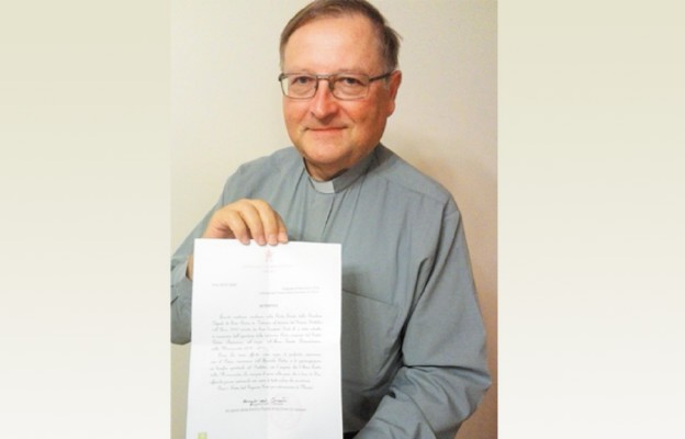 Proboszcz ks. Stanisław Mika prezentuje dokument potwierdzający autentyczność szczególnego daru