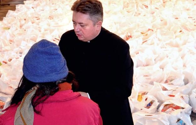 Ks. Dariusz Amrogowicz rozdaje paczki Caritas w czasie wigilii dla bezdomnych