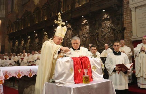 Abp Józef Kupny wlewa wonności do oleju i przyrządza krzyżmo
