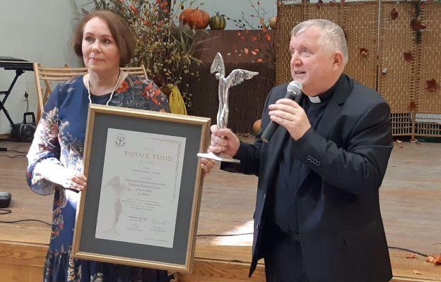 Jadwiga Leśniewska i ks. Tadeusz Pajurek prezentują nagrodę