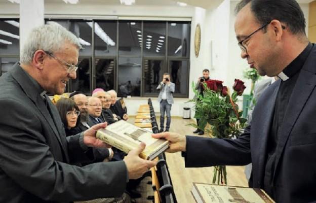 """Ks. Marek Szymański, dyrektor """"Gaudium"""", przekazuje egzemplarz Biblii ks. prof. Antoniemu Troninie"""