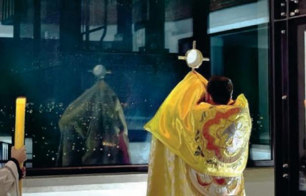 Kapłan błogosławi Najświętszym Sakramentem cztery strony świata z wieży przy Centrum JP II