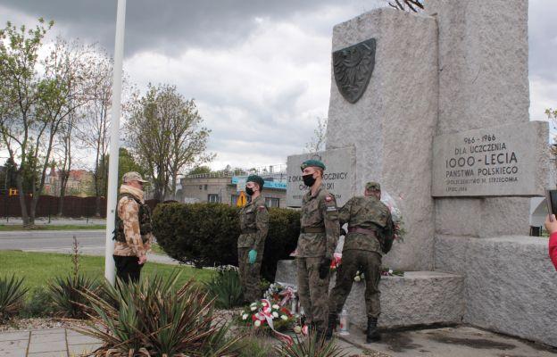 Mieszkańcy składający kwiaty pod pomnikiem.