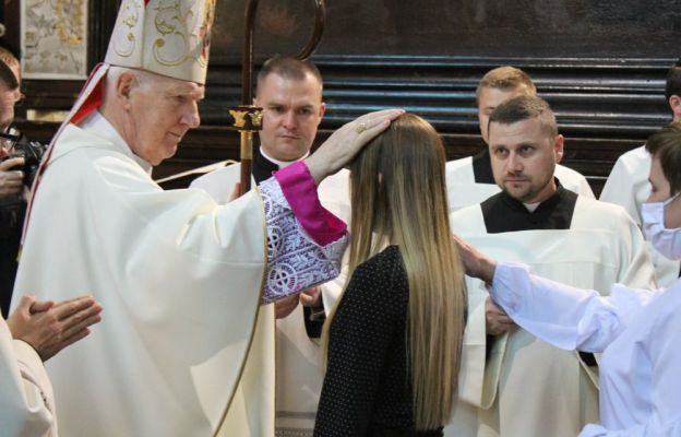 Bp Ignacy Dec namaszcza olejem krzyżma czoła osób bierzmowanych.