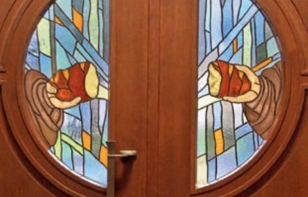 Drzwi wejściowe do kościoła z motywem chleba św. Brata Alberta