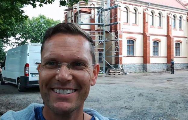 Ks. proboszcz Paweł Wróblewski na tle odrestaurowanej części budynku