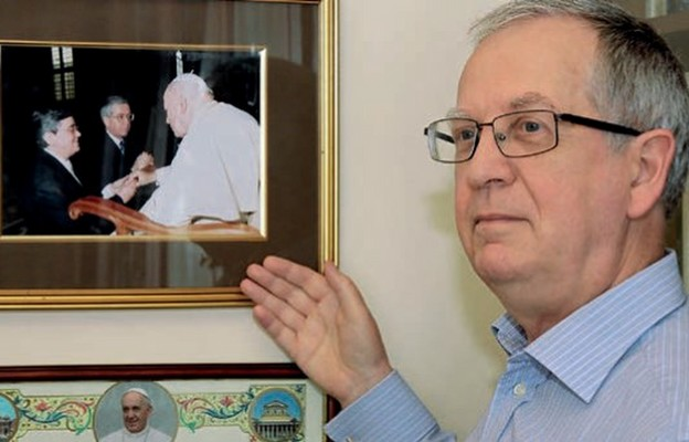 Paweł Gruszczyński na tle fotografii zOjcem Świętym