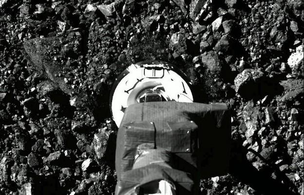 Zdjęcie pamiątkowe z dnia 20 października 2020 r., udostępnione przez NASA 22 października 2020 r., przedstawia stopkę statku kosmicznego OSIRIS-REx, która dotyka powierzchni asteroidy Bennu.