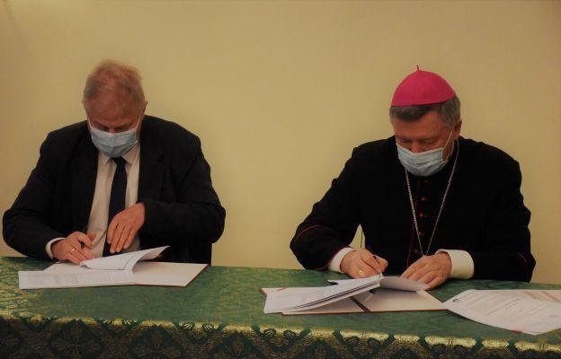 Abp Józef Kupny oraz prezes Maciej Chorowski podpisują stosowne dokumenty