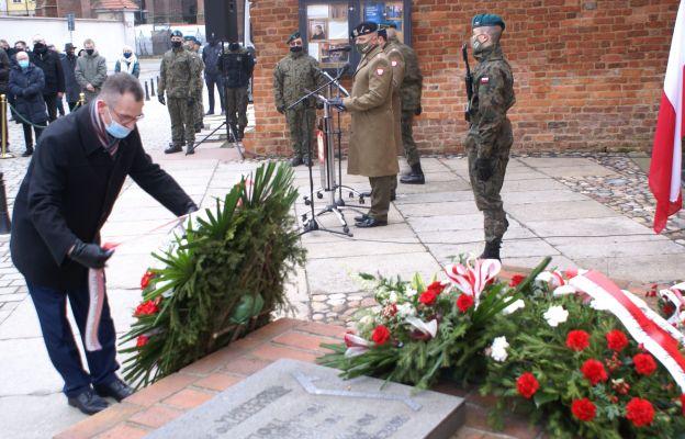 Złożenie kwiatów pod pomnikiem pamięci