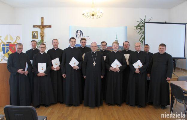 Kapłani po otrzymaniu dekretów stanęli do pamiątkowego zdjęcia z biskupem