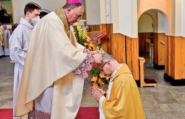 Biskup tarnowski wręcza krzyż misyjny ks. Grzegorzowi