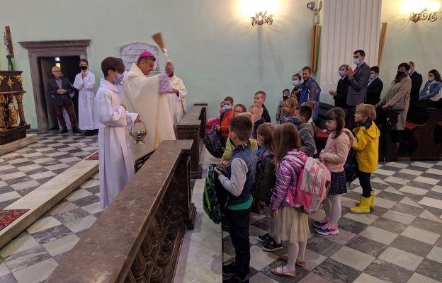 Biskup błogosławi tornistry najmłodszym uczniom.